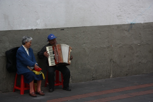 A couple sings and plays accordion in the Old Town streets of Quito