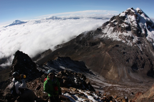 Making the final push to the summit with Illiniza Norte and Cotopaxi in the background